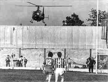 GAA Players take to the field amid British Army Activity in the base behind the goals.